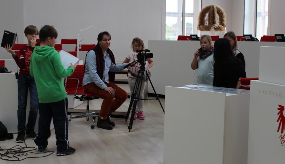 Kinderreporter_innen filmen im Brandenburger Landtag, begleitet von Bildungsreferent Frank Hofmann